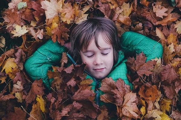 Enfant allongé dans un tas de feuilles mortes